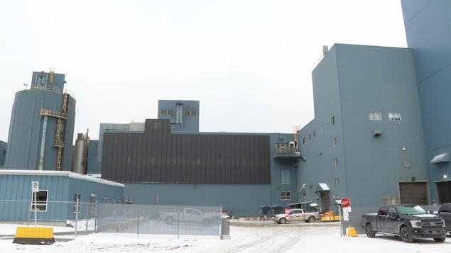 Le panneau est installé à la vertical sur le côté d'un bâtiment de la minière.
