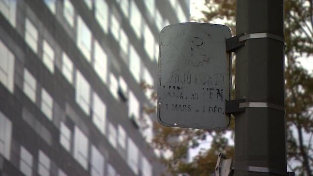 Un panneau de stationnement usé rendu illisible à Montréal.
