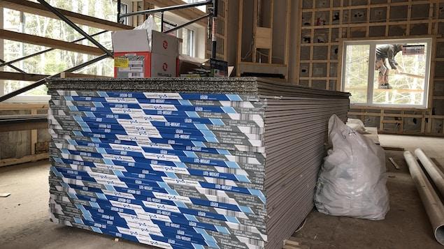Une pile de panneaux de gypse dans une maison en construction.
