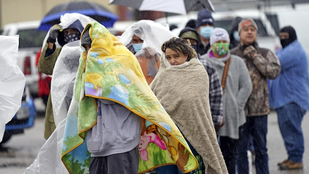 Des gens, visiblement gelés, font la queue, certains tentant de se réchauffer en s'emmitouflant dans des couvertures.