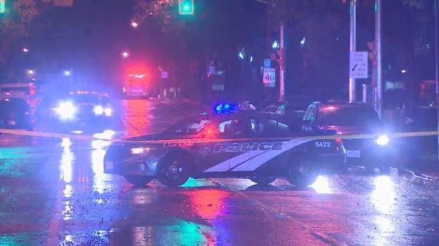 Des voitures de police la nuit bloquent une rue.