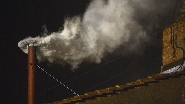 La fumée s'échappe en pleine nuit d'une mince cheminée rouge.