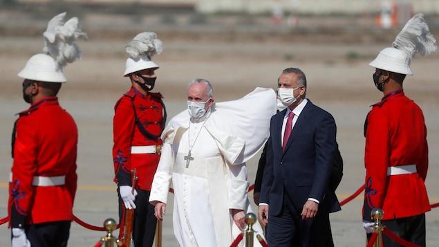Les deux hommes marchent entourés d'un cordon d'honneur de gardes irakiens.