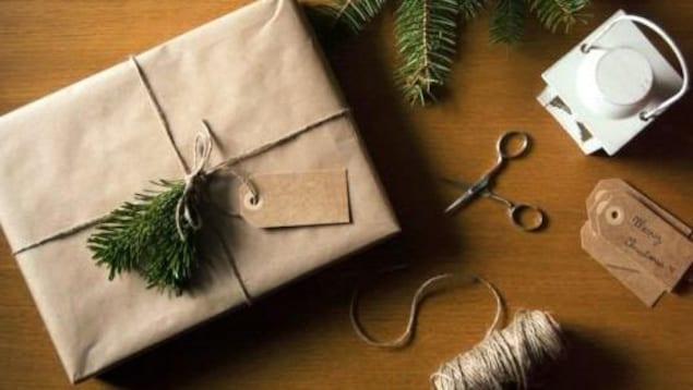 Cadeau emballé dans du papier brun, avec de la ficelle et une branche de sapin.