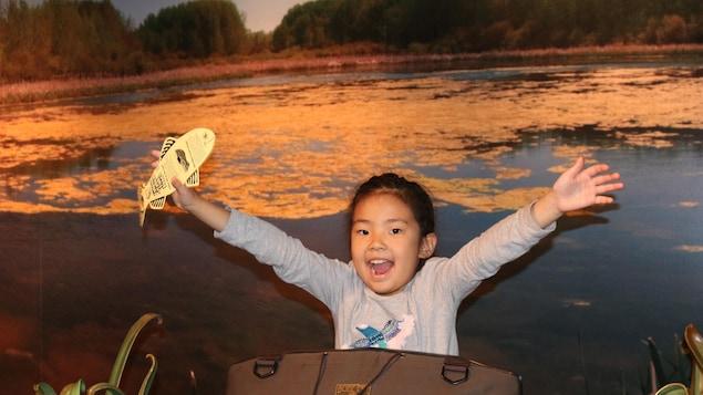 Une petite fille tient un poisson en carton dans sa main.
