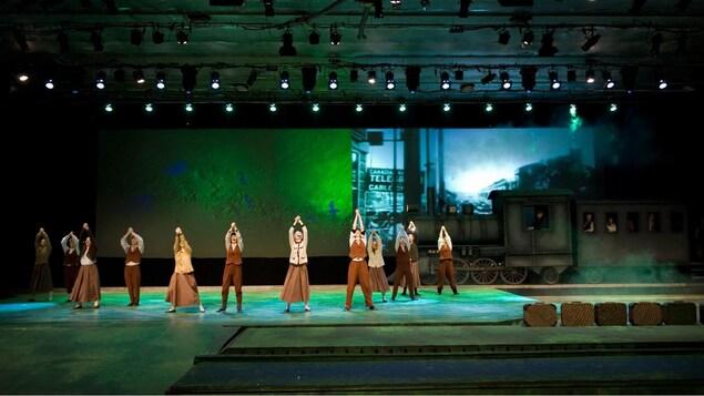 Une dizaine de comédien chantent et dansent sur scène. Un train et des valises composent le décor.