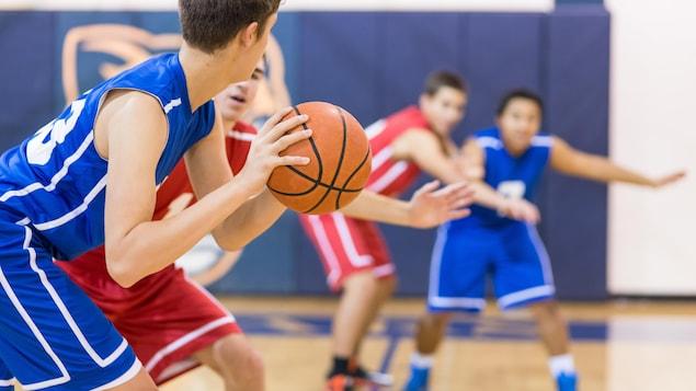 Des adolescents jouent au basketball dans un gymnase.