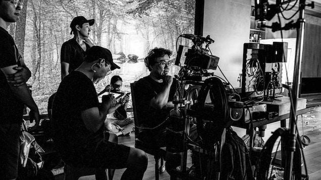 Photo en noir et blanc montrant Bong Joon-ho sur le plateau de tournage.