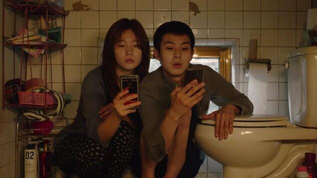 Un adolescent et une adolescente regardent leur cellulaire en étant accroupis à côté d'une toilette.
