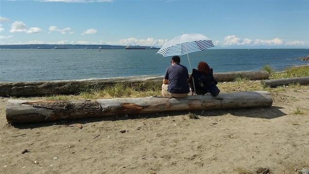 Un couple sur une plage de West Vancouver à l'ombre d'un parasol