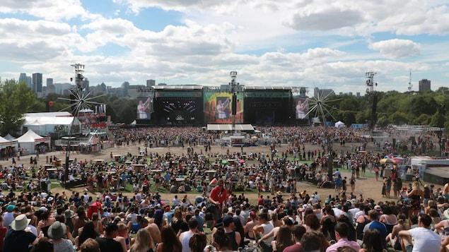 Des milliers de personnes rassemblées devant une scène et des écrans géants.