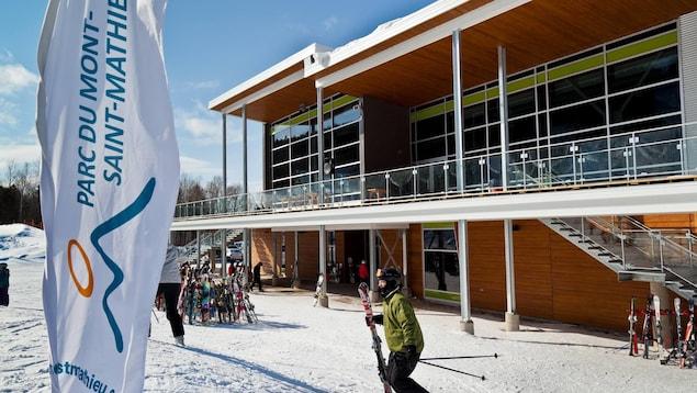 Un skieur se trouve devant le bâtiment principal du Parc du Mont-Saint-Mathieu.