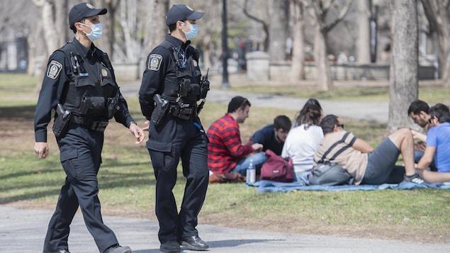 Des policiers passe près d'un groupe de jeunes peu distancés.
