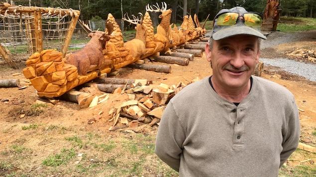 Un homme qui porte une casquette à côté d'une sculpture en bois