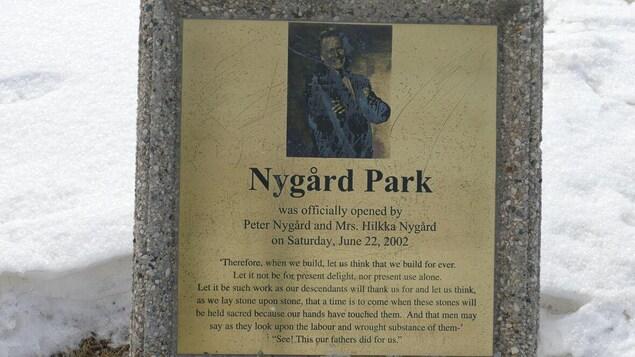 Plaque commémorative sur laquelle se trouvent le nom du parc Nygard, et une photo de Peter Nygard.