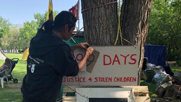 Un homme ajoute ajoute un quatre-vingt-dix-neuf sur un panneau accroché à un arbre et entouré de pancartes de revendication