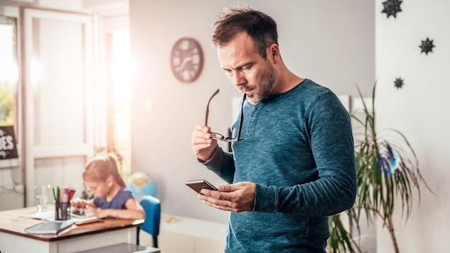 Un père regarde son téléphone avec un air inquiet pendant que sa fille fait ses devoirs en arrière-plan.