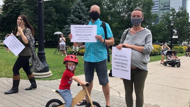 Deux parents et leur enfant posent avec des pancartes pour la caméra.