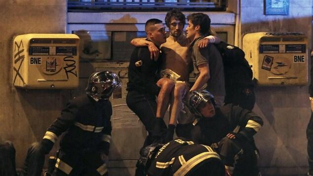Des pompiers viennent en secours à un homme blessé près de la salle de concert du Bataclan, à Paris, lors des attaques du 13 novembre 2015.