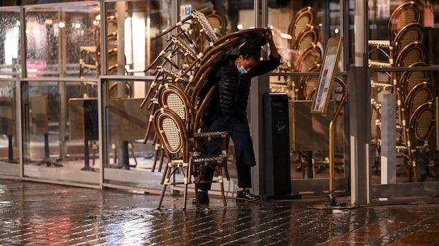 Une femme portant un tas de chaises d'une terrasse.