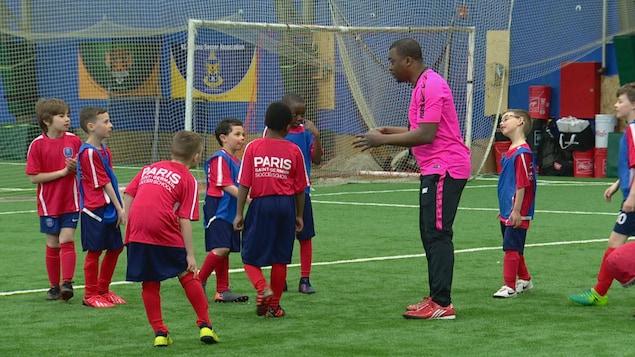 Des enfants en maillot de soccer écoute leur entraîneur sur un terrain.
