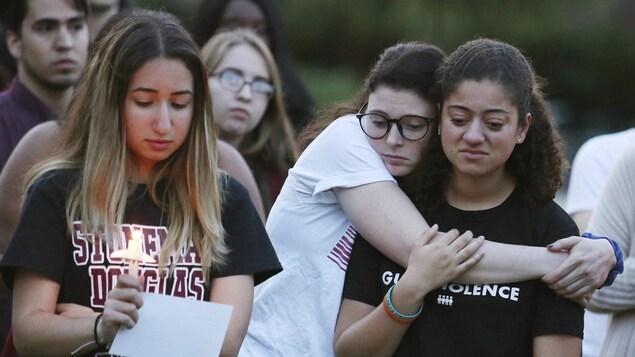 Deux jeunes filles se serrent dans leur bras, la mine triste. Une autre, à leurs côtés, tient une bougie et une photo dans ses mains.