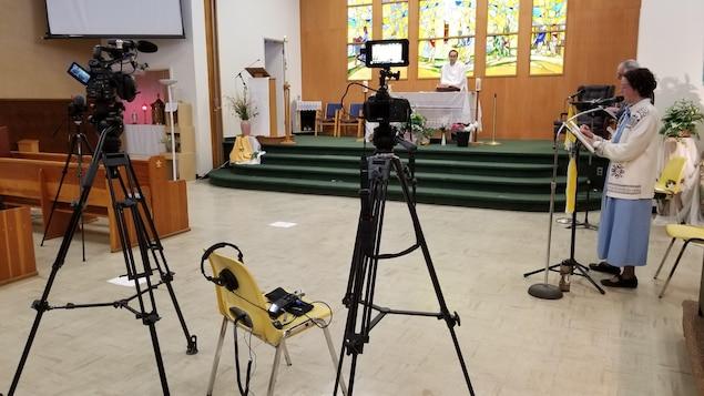 Dans une église, des caméras filment un abbé et des chanteurs, tous à bonne distance les uns des autres.