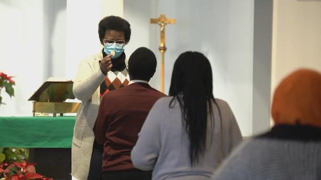 Des fidèles font la queue pendant que l'hostie est donnée à la paroisse Saint-Thomas d'Aquin à Edmonton.