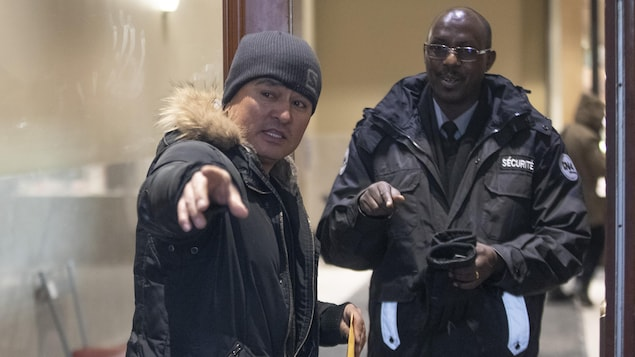 Un homme explique quelque chose à un agent de sécurité en pointant devant lui.