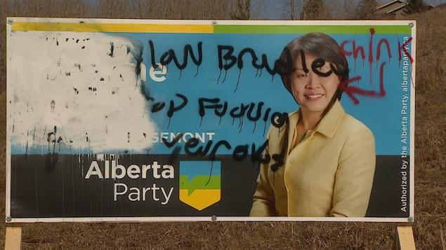 Vue sur une pancarte avec le visage d'une candidate. Elle a des traits asiatiques. Autour de son visage on voit des propos racistes ajoutés par graffiti.