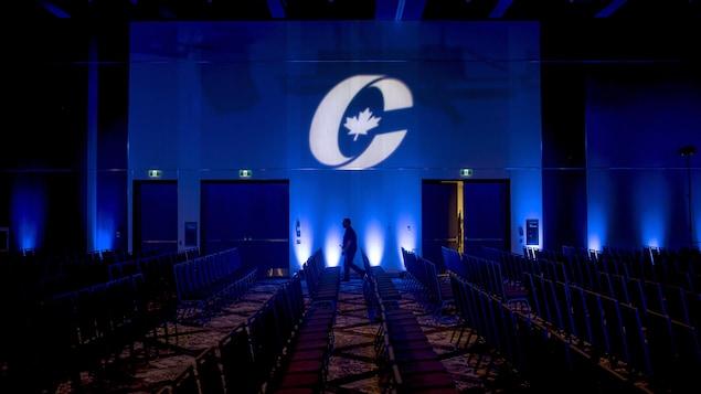 Une salle remplie de chaises vides. Le logo du Parti conservateur du Canada est projeté sur le mur.
