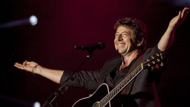 Le chanteur Patrick Bruel salue la foule sur les Plaines présente malgré la pluie.