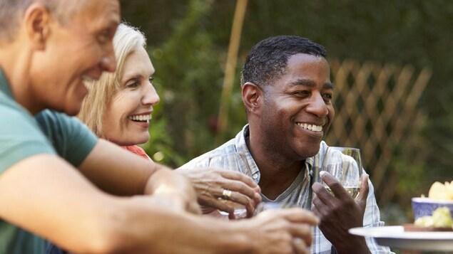 Deux hommes et une femme rient et boivent autour d'une table en extérieur.