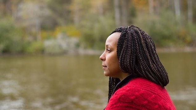 Une dame regarde le large, près d'une rivière.