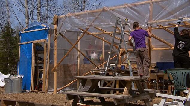 Des occupants du campement près d'un chemin d'accès au site Galt de la pétrolière Junex travaillent sur leurs installations. Un homme avec un marteau clou un pellicule imperméable sur une structure de bois.