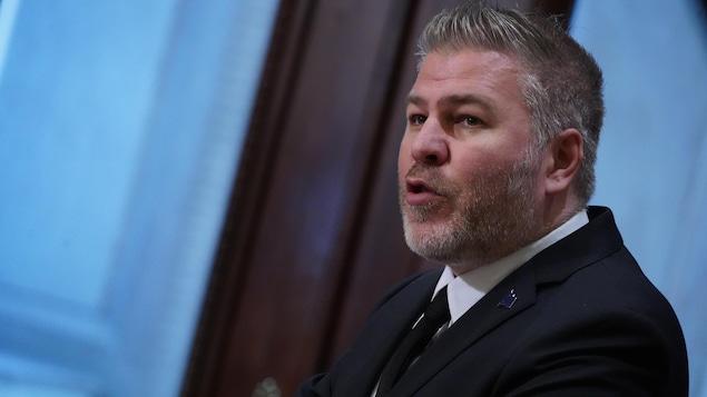 Un homme portant la barbe et un veston avec une cravate parle.