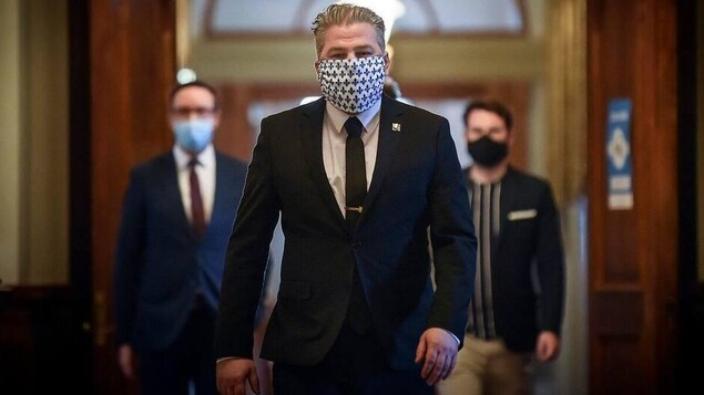 Pascal Bérubé porte un masque et marche dans un couloir de l'Assemblée nationale.