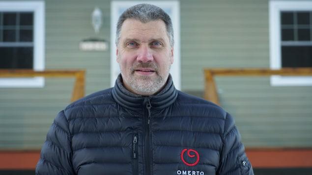 Un homme devant une maison