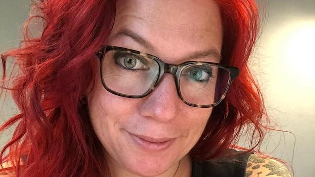 Une femme avec des lunettes et des cheveux rouges regarde la caméra.