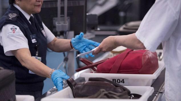 Photo d'un passager qui montre sa carte d'embarquement à une employée de la sécurité.