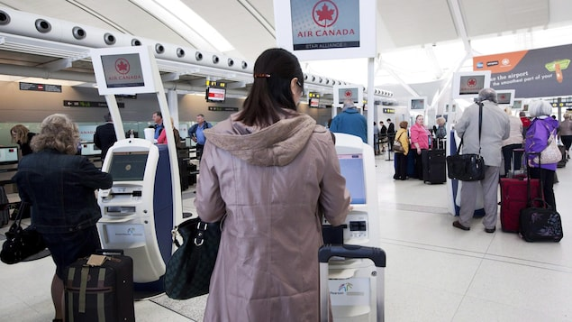 Des voyageurs s'enregistrent à un kiosque.