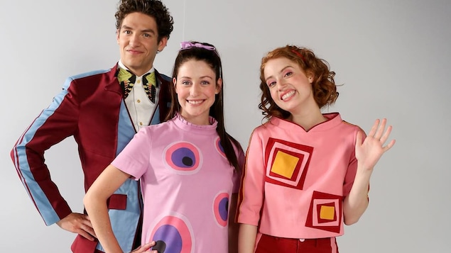 Les trois acteurs sont habillés avec les anciens vêtements colorés de Passe-Partout.
