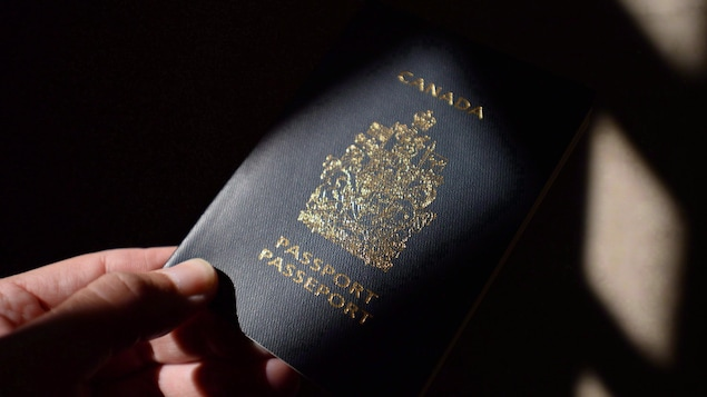Une main qui tend un passeport canadien.