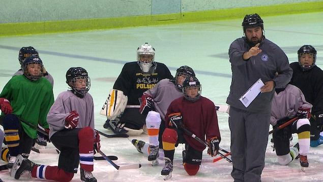 Des joueurs et un entraîneurs sur la glace.