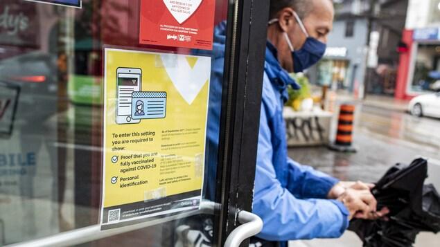 Un client sort d'un restaurant à Toronto. Une affiche sur la porte indique que le passeport vaccinal y est exigé maintenant.