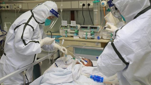 Du personnel médical, qui porte une combinaison protectrice, prodigue des soins à un patient.