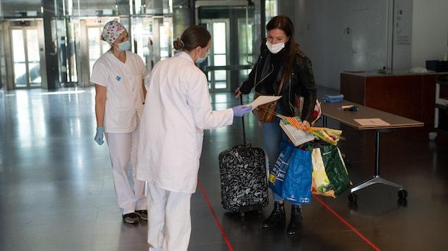 Des travailleuses de la santé offrent un livre et une rose à une patiente guérie de la COVID-19 qui quitte un hôtel avec ses bagages.