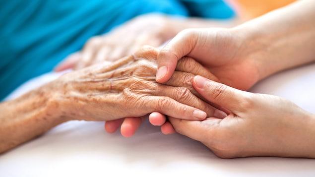 La main d'une femme âgée alitée repose dans la main d'une personne plus jeune.