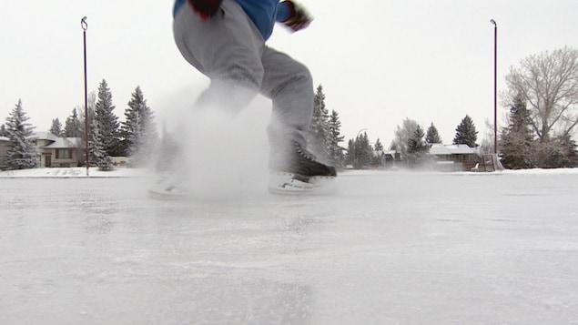 Un homme fait voler la glace en freinant sur une patinoire extérieure.