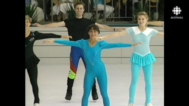Quatre patineurs en prestation sur une patinoire intérieure, dont deux portant des léotards fluos